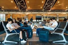 Nicht identifizierte Leute, die in Einstiegtoraufenthaltsraum im Flughafen warten Lizenzfreie Stockfotos