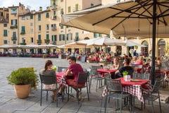 Nicht identifizierte Leute, die traditionelles italienisches Lebensmittel in r im Freien essen stockbild