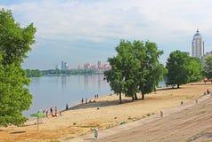 Nicht identifizierte Leute stehen auf dem Strand von Dnipr-Fluss in Obolon-Bezirk still Stockbild