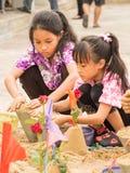 Nicht identifizierte Mädchen, die Sandpagoden mit bunten Flaggen herein so machen Lizenzfreie Stockfotografie