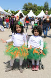 Nicht identifizierte nette kleine Mädchen mit Ballettröckchen umsäumt die Aufstellung am orange Blüten-Karneval Stockfotografie