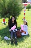 Nicht identifizierte Schwestern, die auf Gras sitzen und ihre Zuckerwatten genießen Lizenzfreie Stockfotos