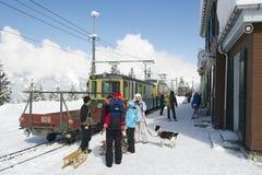 Nicht identifizierte Touristen mit Hornschlitten warten auf den Zug an Wengernalpbahn-Bahnstation in Grindelwald, die Schweiz lizenzfreies stockfoto