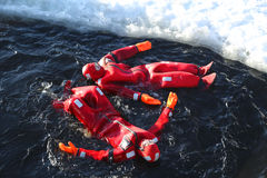 Nicht identifizierte Touristen oben übersetzt mit einem Überlebensklagen-Eisschwimmen in gefrorener Ostsee Lizenzfreies Stockbild