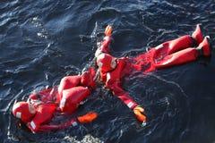 Nicht identifizierte Touristen oben übersetzt mit einem Überlebensklagen-Eisschwimmen in gefrorener Ostsee Stockfotografie