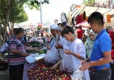 Nicht identifizierte Usbek- und Afghaneimmigranten, die rote Pflaumen am Landwirtmarkt kaufen Stockbild