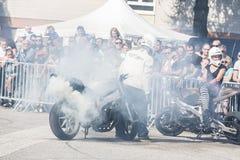 Nicht identifizierter Bremsungsreiter macht das Dia, das auf der Straße slinding ist Mit Los Rauche lizenzfreie stockfotos