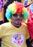 Nicht identifizierter Clown mit der bunten Perücke, die am orange Blüten-Karneval aufwirft Lizenzfreie Stockfotografie