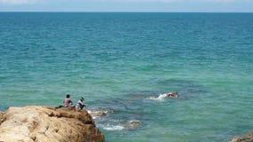 Nicht identifizierter Fischer zwei, der auf einem braunen Felsen in dem Ozean sitzt stock video