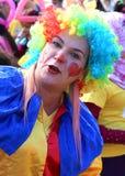 Nicht identifizierter Frauen-Clown mit der bunten Perücke, die am orange Blüten-Karneval aufwirft Stockfoto