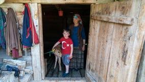 Nicht identifizierter Junge mit seiner Mutter und einem Kalb am Keller ihres hölzernen Hauses in Misirli-Dorf, Artvin, die Türkei lizenzfreie stockbilder