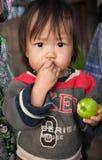 Nicht identifizierter kleiner Karen-Junge, der Affeapfel isst Stockbilder