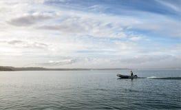 Nicht identifizierter Mann fährt ein Pontonboot Lizenzfreie Stockfotos