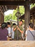 Nicht identifizierter Mannversuch, zum einer schweren Muskatblüte in kiyomizu Tempel zu halten Lizenzfreie Stockfotografie