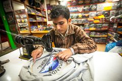 Nicht identifizierter Nepalimann tut Stickerei auf Kleidung in einer kleinen Werkstatt lizenzfreies stockfoto