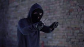 Nicht identifizierter Räuber mit dem erpressenden Geld des Messers, drohend durch Waffe, Einbruch stock video footage