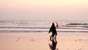 Nicht identifiziertes Frauentanzen mit Fan auf dem Strand stock footage