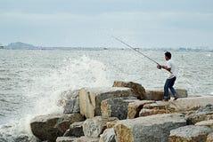 Nicht identifiziertes Mannfischen mit dem großen Wellenspritzen Stockfotos