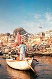 Nicht identifiziertes Mannruderboot auf dem Fluss der Ganges nahe heiligen ghats mit Leuten in Varanasi, Indien Stockfoto