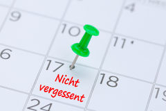 Nicht vergessent written on a calendar with a green push pin to Royalty Free Stock Images