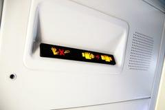 Nichtraucher und befestigen Sie Sicherheitsgurt Zeichen innerhalb eines Flugzeuges Stockfotos