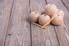Niciani gejtawy Piłki przędza i dziewiarskie igły dla dziać na drewnianym tle fotografia stock