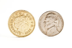 Nickel and Pound. Nickel and One English pound face off standing on the edge stock photo