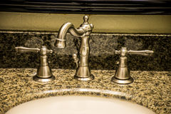 Nickle bathroom fauctet. A granite bathroom sink with a shiny silver modern yet old fashioned faucet stock photography