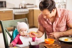 Único pai que alimenta sua filha do bebê em casa Imagens de Stock