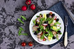 Nicoise salad with tuna, egg, cherry tomatoes and black olives. On grey dark background. French cuisine. Top view, copy space Royalty Free Stock Images