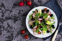 Nicoise salad with tuna, egg, cherry tomatoes and black olives. On grey dark background. French cuisine. Top view, copy space Royalty Free Stock Photography