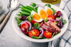 Nicoise sallad med tonfisk, ansjovisar, ägg, haricot vert, oliv, tomater, röda lökar och salladsidor Royaltyfria Bilder