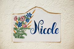 Nicole - vieux tuile sur le mur de rue de ville avec la fleur et beau Photo libre de droits
