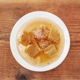 Nid d'abeilles dans le plat blanc de porcelaine sur le Tableau en bois, vue supérieure Photo stock