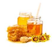 Nid d'abeilles doux et deux pots de miel avec le bâton et les fleurs Photo stock