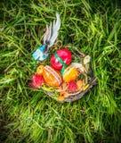 Nid de Pâques avec décorer les oeufs et l'herbe bleue d'oiseau au printemps Images stock