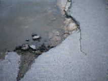 Nid de poule criqué et cassé d'asphalte avec de l'eau sur la surface de images stock