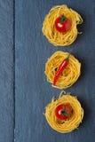 Nid italien de pâtes d'oeufs avec les tomates-cerises et le piment, concept Image stock