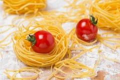 Nid italien de pâtes d'oeufs, tomates-cerises sur une planche à découper Image stock