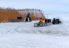 Fishermen on the ice ready to go in the electric sled farther from shore, snowmobiles for winter fishing stock photo