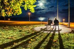 Nida at night. Man sitting next to sculpture of Vytautas Kernagis Royalty Free Stock Photos