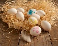 Nido con le uova bianche e le uova dipinte Fotografie Stock Libere da Diritti
