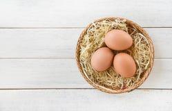 Nido della merce nel carrello delle uova del pollo su fondo di legno bianco fotografia stock