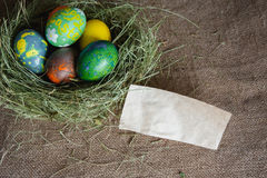 Nido di fieno con le uova di Pasqua e una nota Fotografia Stock