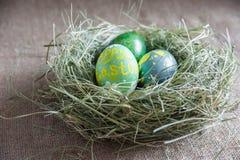 Nido di fieno verde con le uova di Pasqua Fotografia Stock Libera da Diritti