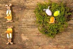 Nido di Pasqua con le uova ed i coniglietti di pasqua dipinti Fotografia Stock