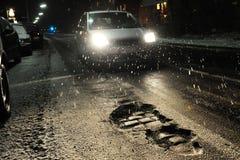 Nids de poule avec la voiture la nuit image stock