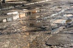 Nids de poule sur la route goudronnée remplie avec de l'eau Photographie stock libre de droits