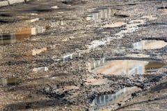 Nids de poule sur la route goudronnée remplie avec de l'eau Photos stock