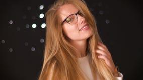 Nieśmiała caucasian kobieta jest ubranym widowiska pokazuje ona ufne emocje i chuje za jej pięknym włosy i